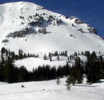 Mount McDougal towers over a snowmobiler in the Wyoming Range